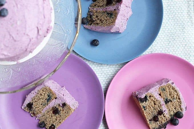 sliced first birthday cake with blueberries on colorful plates
