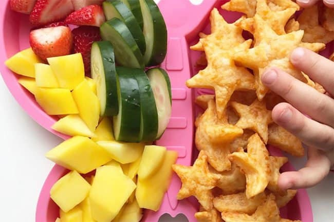 cheesy crackers meal with toddler hand