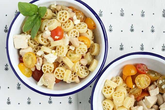 wagon wheel pasta salad in white bowl with blue rim