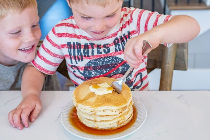 two boys with stack of pancakes