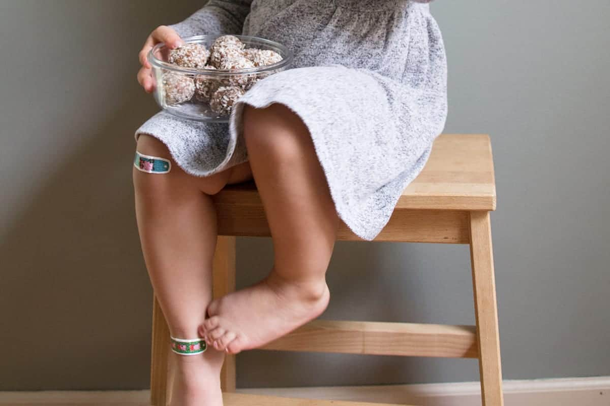 toddler-with-energy-bites-on-stool
