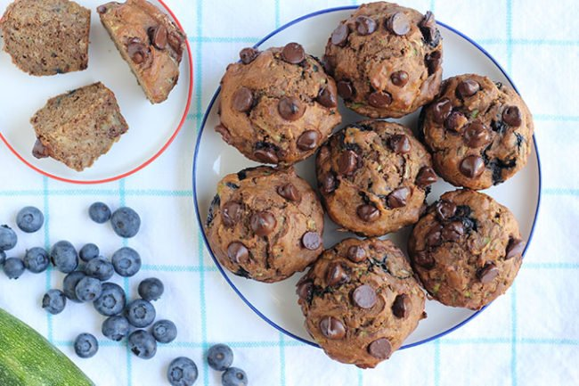 chocolate chip zucchini muffins with berries on towel