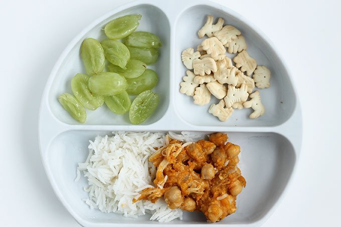 chicken and beans with rice and grapes on kids plate