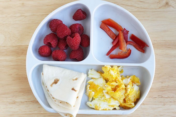 egg tacos with fruit on white divided plate