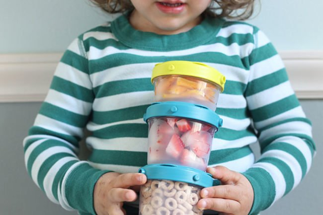 toddler holding snack cups