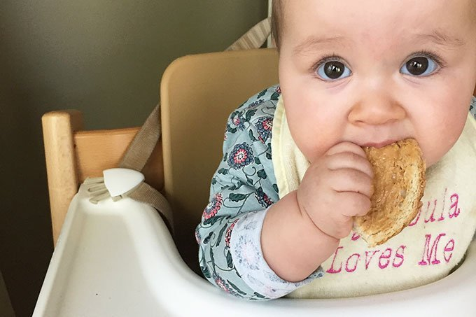 baby eating peanut butter toast