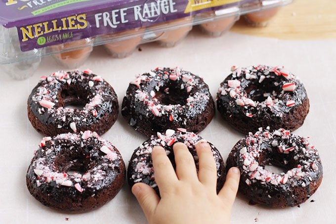 baked chocolate donuts with crushed candy cane and child's hand