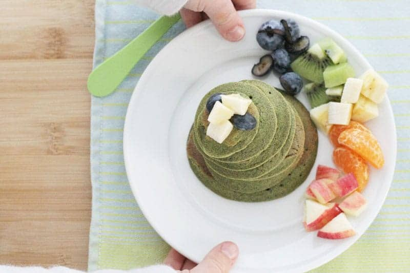 spinach banana pancakes on plate with fruit