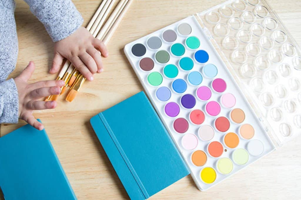 watercolors with toddler hand