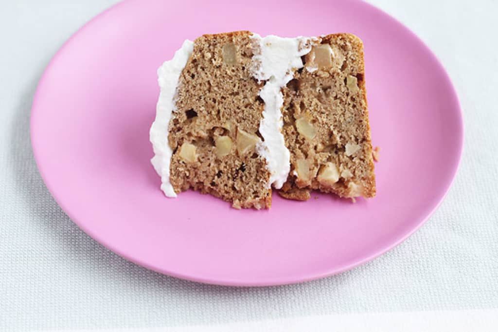 slice of healthy apple cake with frosting on pink plate