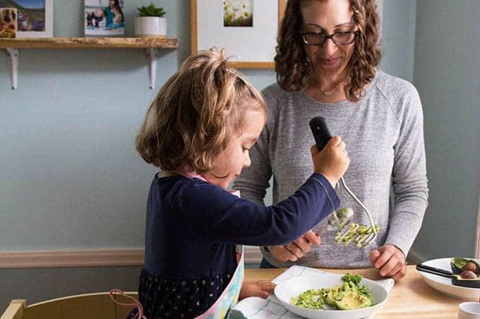 toddler mashing avocado