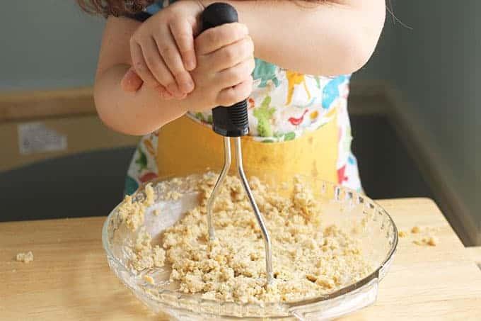 toddler mashing beans
