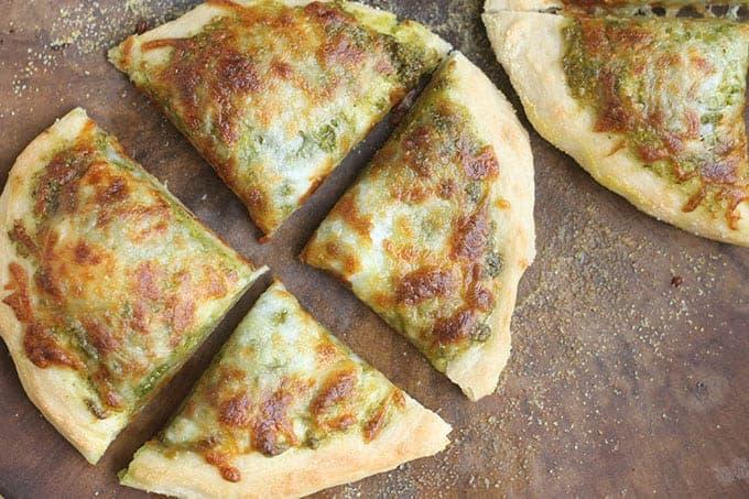pesto-pizza-sliced-on-baking-stone
