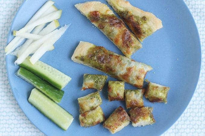 sliced-pesto-pizza-on-blue-plate