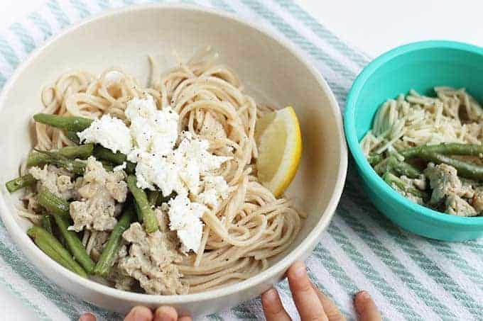 spaghetti with sausage and feta in white bowl