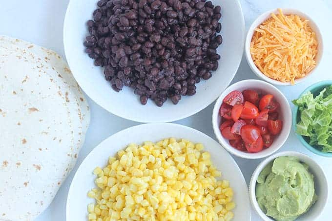 ingredients for taco buffet in white bowls