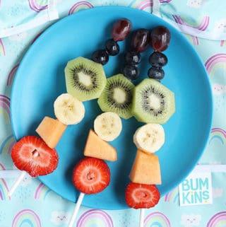 rainbow-fruit-sticks-on-blue-plate