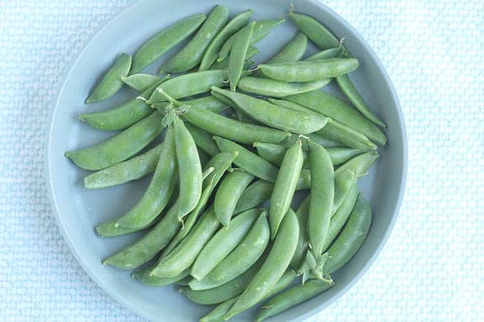 raw snap peas on blue plate