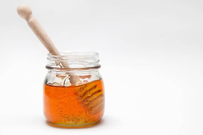 honey in jar on white background