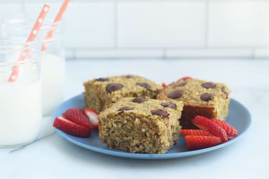 zucchini banana bread squares on plate with milk cups