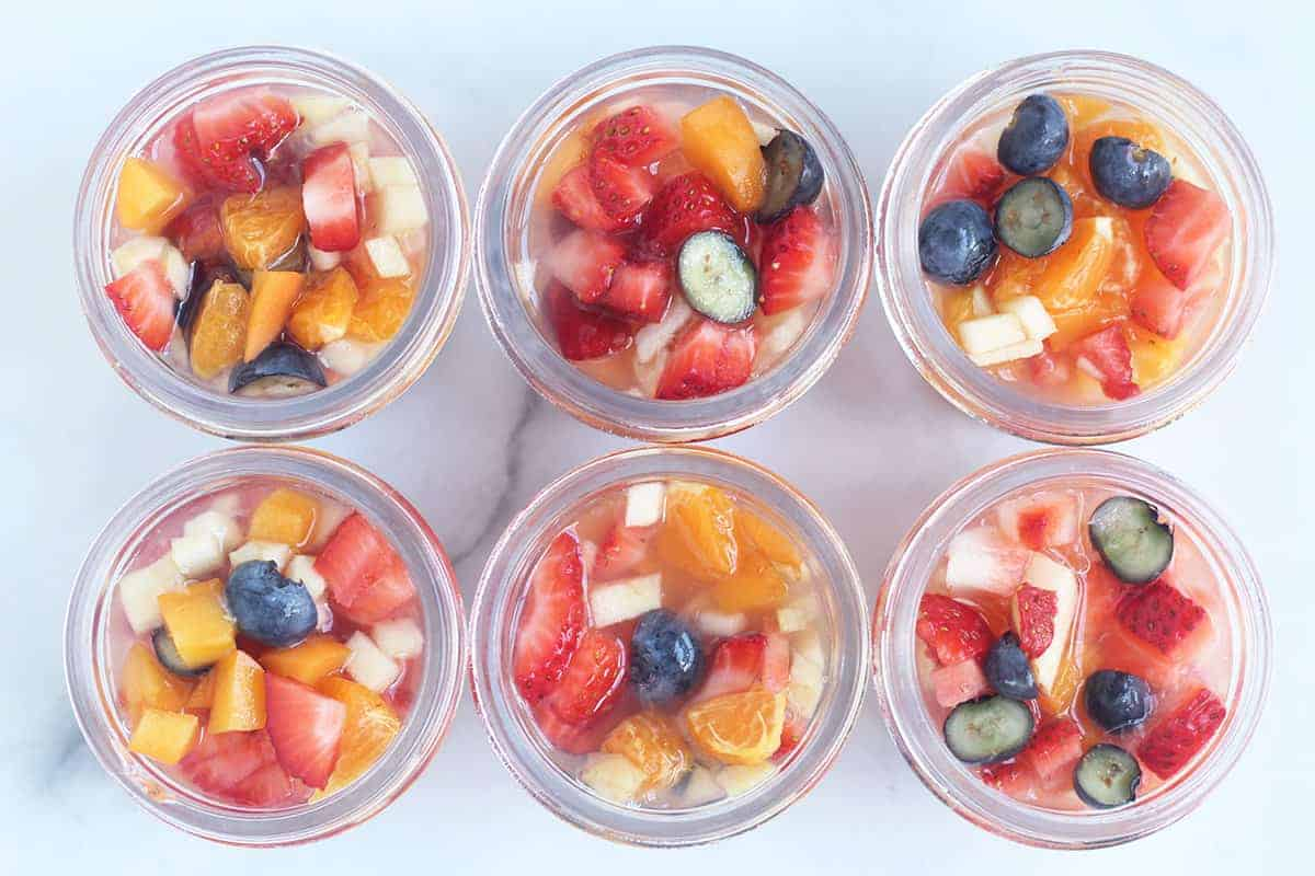 fruit cups in glass jars on counter