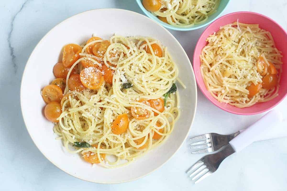 cherry tomato pasta in adult bowl and kid bowls