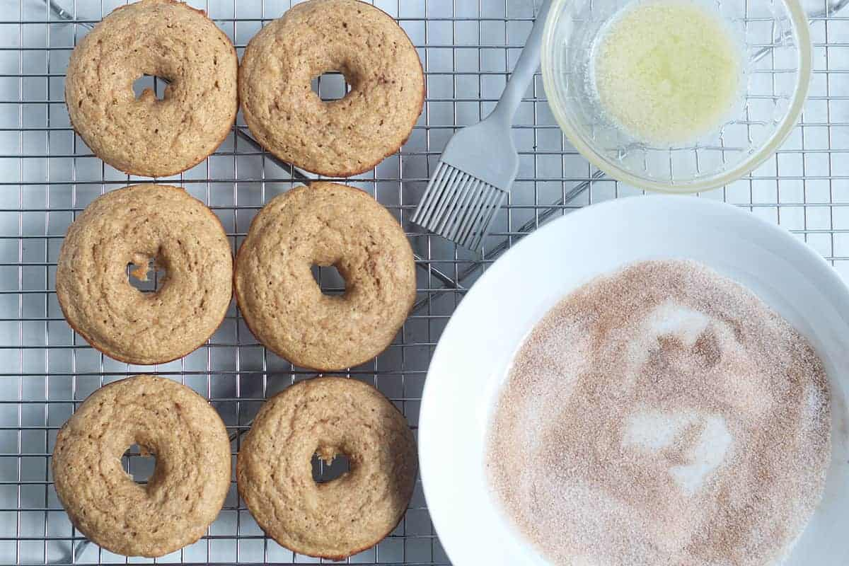 cinnamon sugar with apple donuts on wire rack