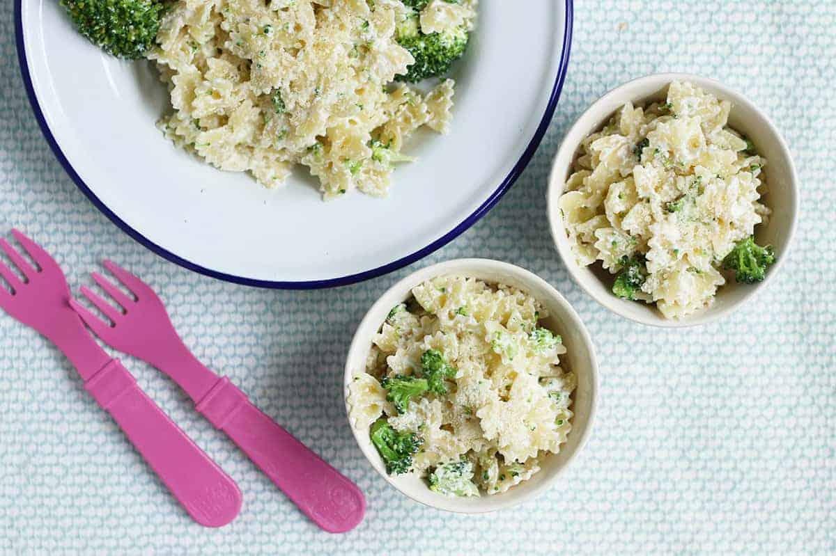 creamy broccoli pasta in white bowls