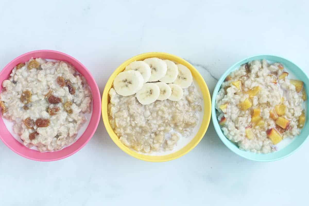 oatmeal with fruit in three kid bowls