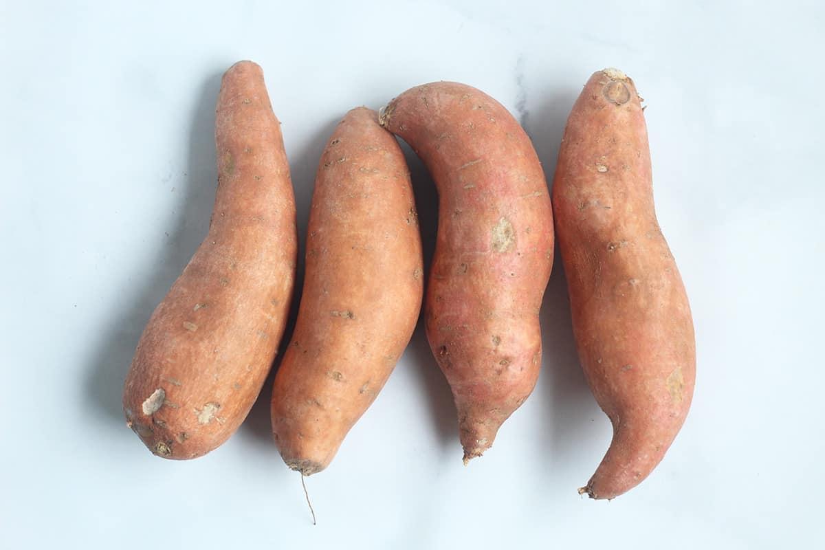 sweet potatoes on white cutting board