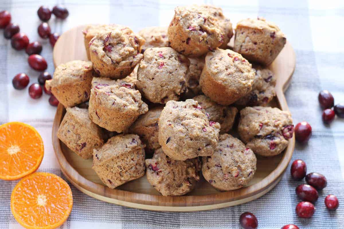 cranberry orange muffins on wooden plate