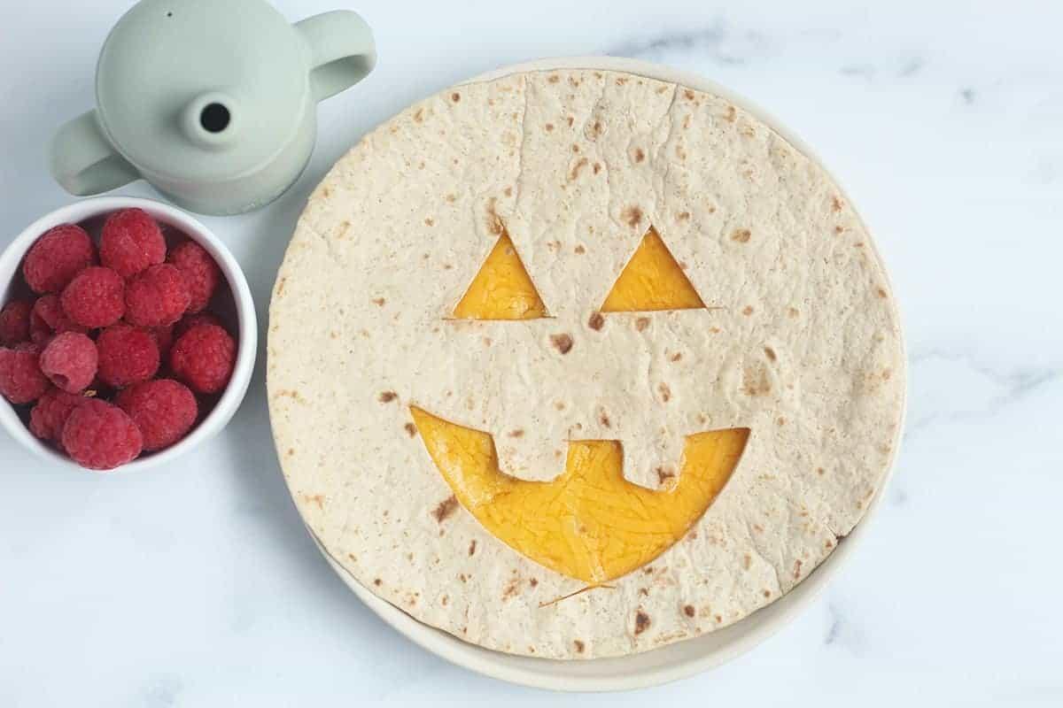 pumpkin quesadilla on plate with raspberries