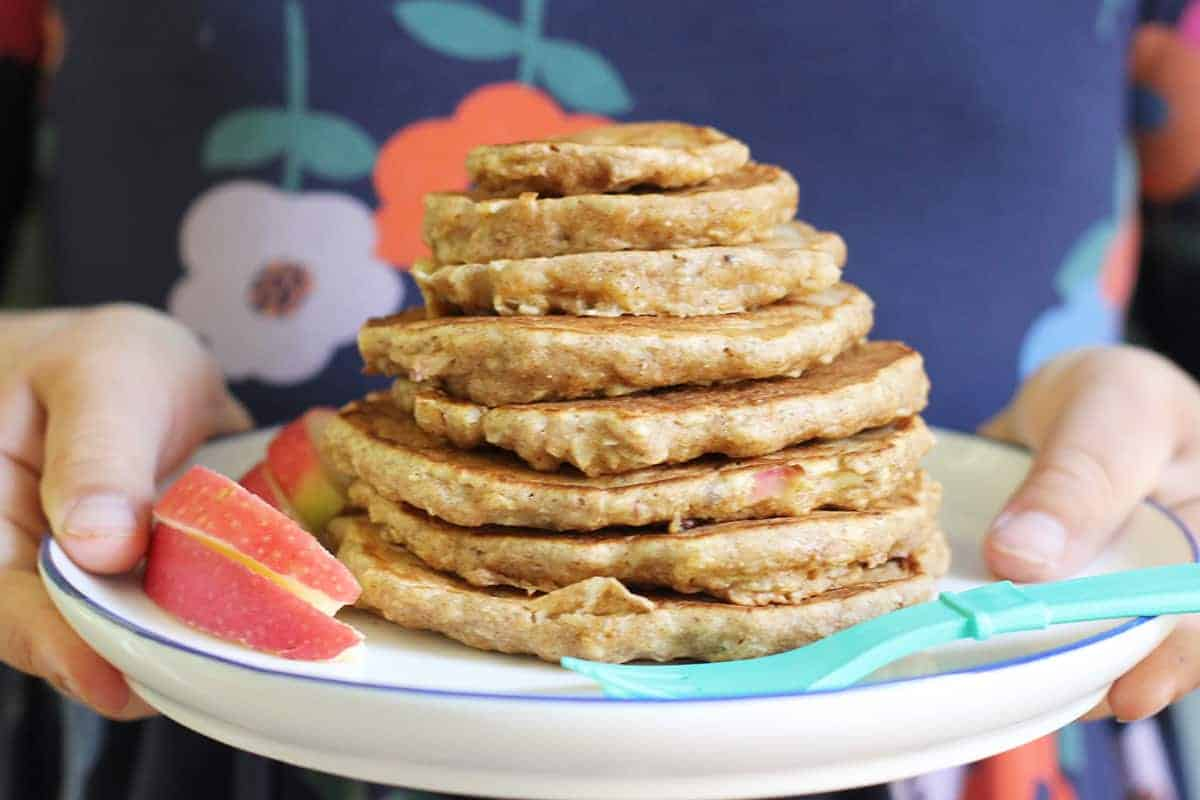 stack of apple pancakes in kids hand