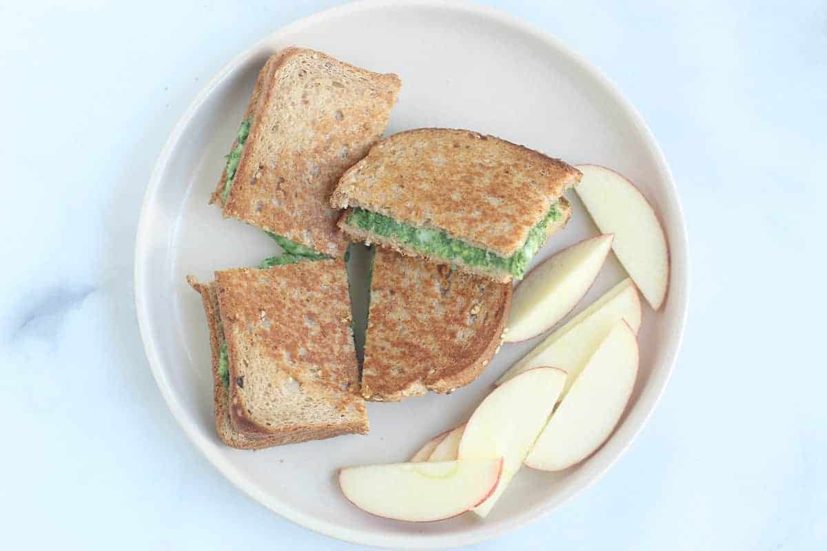 spinach grilled cheese on plate with apple slices